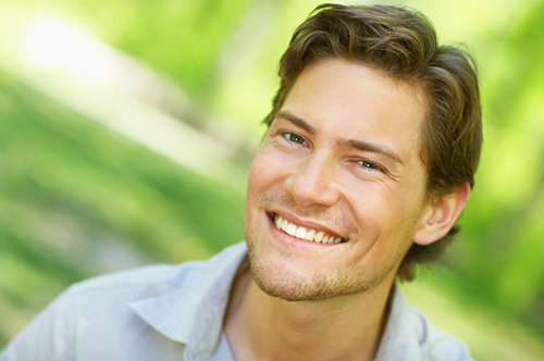 Young man smiling with green natural background iStock 000003447076Small width of 500 pixels